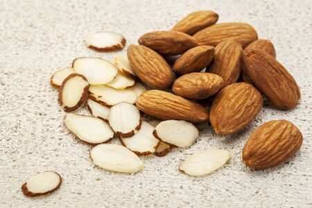 sliced and whole raw almonds on a white painted rough wood barn background Stok Fotoğraf