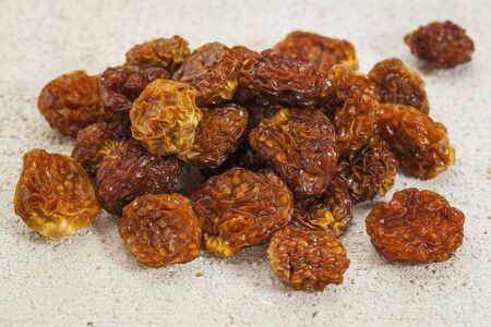 superfruit: dried goldenberries  physalis peruviana  , superfruit from Peru rich in antioxidnats, vitamin A, bioflavonoids, and dietary fiber, white barn wood background