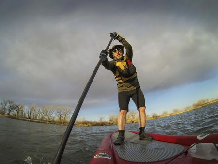 paddleboard: mature male paddler enjoying workout on stand up paddleboard (SUB), calm lake in Colorado, early spring