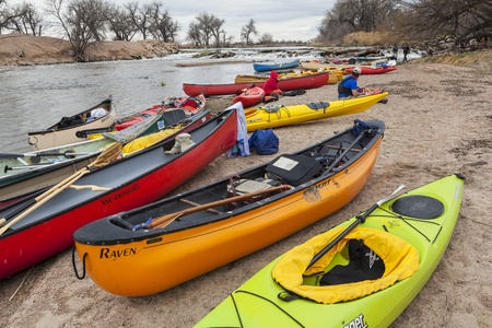 SOUTH PLATTE RIVER, EVANS, COLORADO - APRIL 6: Kayaks and canoes on a river shore below diversion dam during Annual All Club Paddle on April 6, 2013, a popular season opening paddling trip in northern Colorado.