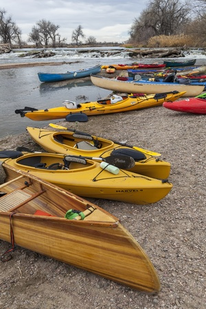 evans: SOUTH PLATTE RIVER, EVANS, COLORADO - APRIL 6: Kayaks and canoes on a river shore below diversion dam during Annual All Club Paddle on April 6, 2013, a popular season opening paddling trip in northern Colorado.