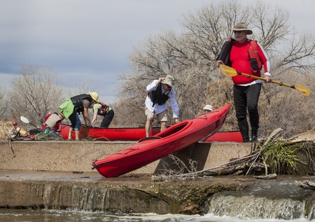 SOUTH PLATTE RIVER, EVANS, COLORADO - APRIL 6: Portaging kayak and canoes over a river diversion dam during Annual All Club Paddle on April 6, 2013. It is a popular season opening paddling trip in northern Colorado.