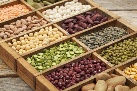 adzuki bean: assorted legumes: green, red and French lentils, soybean, green and yellow pea, fava bean, kidney, mung, adzuki bean  in a wooden box Stock Photo
