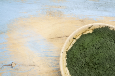 small bowl of Hawaiian spirulina powder against wood background Stock Photo - 19142129