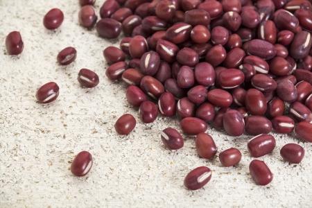 adzuki bean: Japanese adzuki (aduki, azuki) beans on a rough white painted barn wood surface
