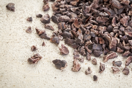 Close-up of a pile of raw cacao nibs on a rough white painted barn wood background Stock Photo - 19323195