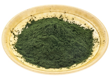 small bowl of Hawaiian spirulina powder against a rough white painted barn wood background Stock Photo