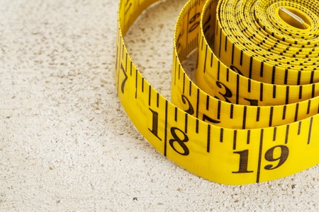 yellow inch tape measure on a rough white painted barn wood background Stock Photo - 19323191