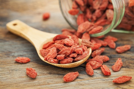 Tibetan goji berries (wolfberry) spilling of the glass jar on a wooden spoon, selective focus Stock Photo - 19323202