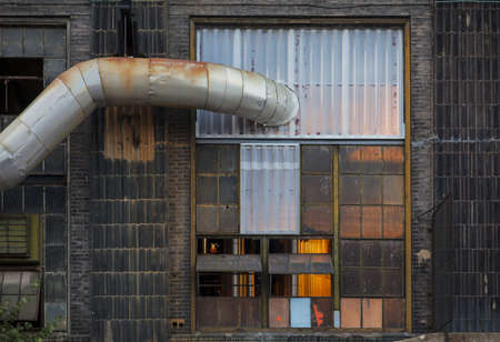industrial building wall with a large window, light inside, pipe, cables Stock Photo - 19323210