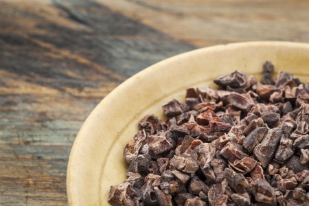 Raw cacao nibs in a small ceramic bowl against grunge wooden background Stock Photo - 19497044