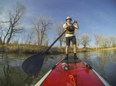 paddler: mature male paddler on a red stand up paddleboard (SUP), calm lake in Colorado, early spring