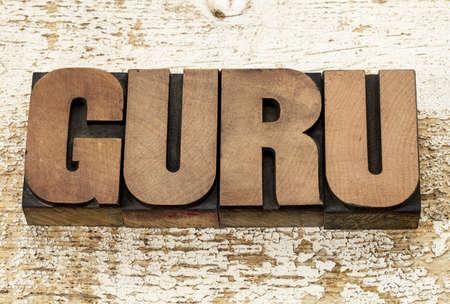 guru: guru word in vintage letterpress wood type blocks against grunge white painted barn wood