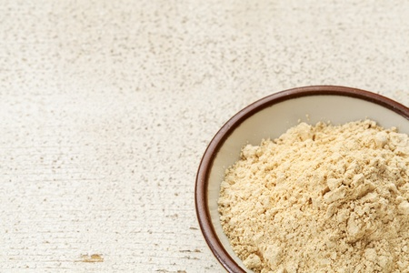 adaptogen: maca root powder (nutrition supplement - superfood from Andies) in a small ceramic bowl on a rustic barn wood Stock Photo