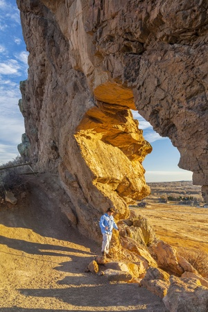 loveland: male hiker looking through a keyhole in Devils Backbone Open Space at foothills of Rocky Mountains