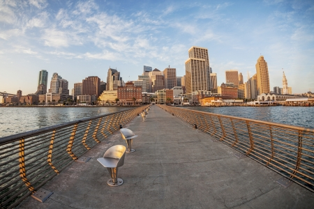 San Francisco cityscape with Ferry Terminal at sunrise from Pier 14 with metal swivel chairs, distorted fish eye perspective from Pier 14 photo
