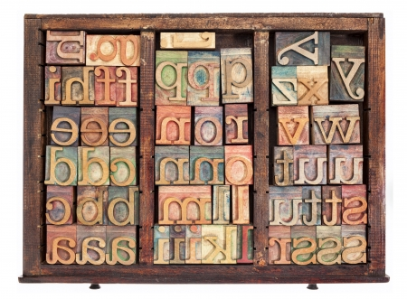 typesetter: alphabet - letterpress wood type printing blocks in old typesetter drawer isolated on white
