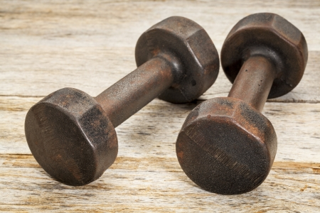 a pair of vintage iron rusty dumbbells on white painted barn wood background - fitness concept Stock Photo - 20046913