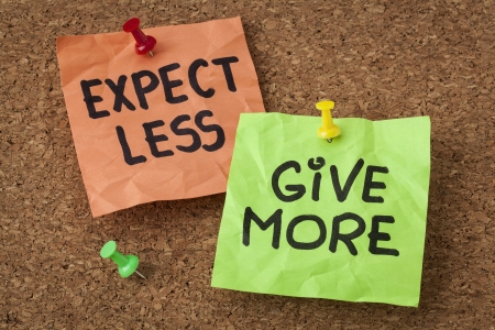 less: expect less, give more - motivation or self improvement concept - handwriting on colorful sticky notes