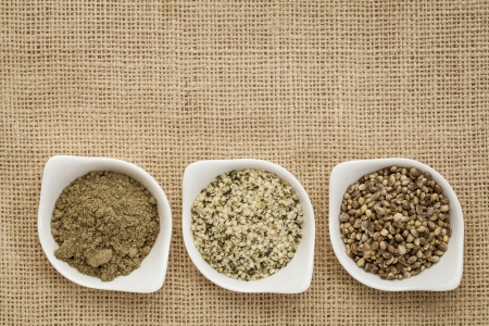 hemp: hemp products: seeds, hearts (shelled seeds) and protein powder in small ceramic bowls on burlap canvas