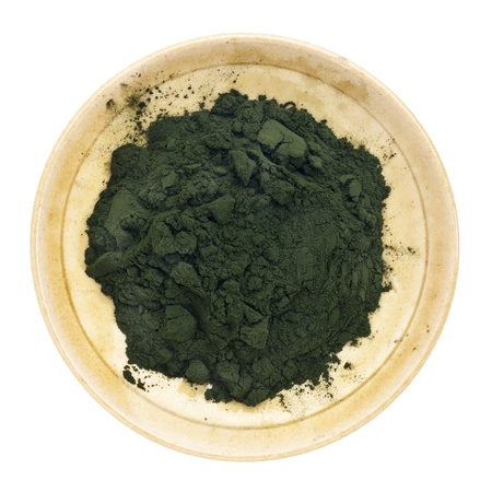 Nutrient-rich organic chlorella powder on a small ceramic bowl, isolated on white, top view Stock Photo