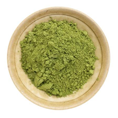 Moringa blad poeder in een kleine keramische kom, geïsoleerd op wit, bovenaanzicht