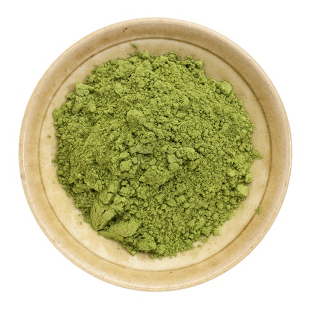 moringa leaf powder in a small ceramic bowl, isolated on white, top view