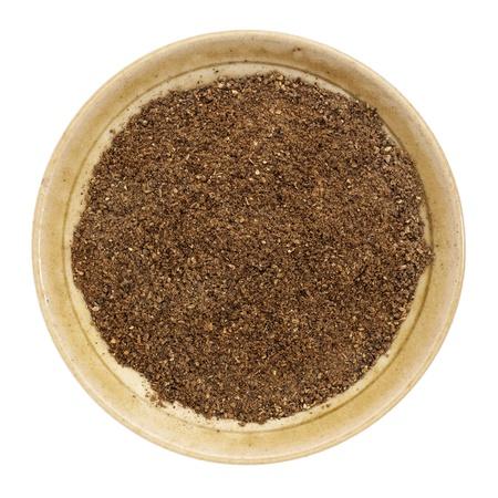 morinda: organic noni fruit powder from Hawaiian evergreen shrub in a small ceramic bowl, isolated on white, top view,