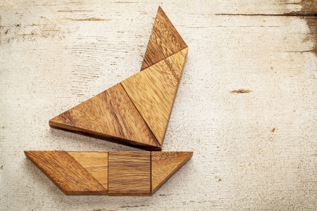 abstract picture of a sailing boat built from seven tangram wooden pieces over a rustic white painted barn wood Stock Photo - 20300426