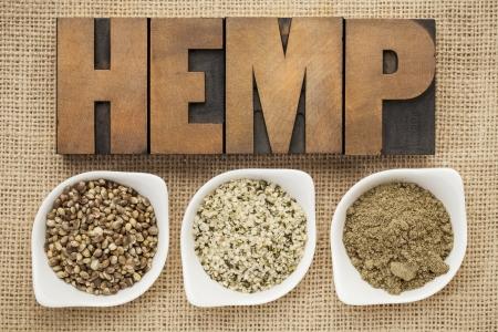 hemp: Hanfprodukte: Samen, Herzen (geschälte Samen) und Protein-Pulver in kleinen Keramik-Schalen auf Sackleinen Leinwand mit Wort Hanf in Hhhochhdruckholztypen geschrieben