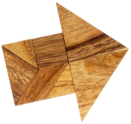 abstract picture of an arrow built from seven tangram wooden pieces, a traditional Chinese puzzle game Stock Photo - 20383198