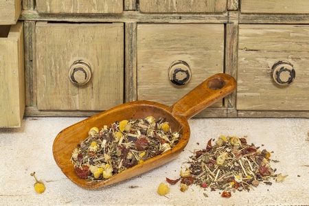 organic herbal tea (chamomile, peppermint,,orange peel, rose hips, hibiscus,) - rustic wooden scoop and a pile on rough white painted barn wood with a primitive apothecary drawer cabinet Stock Photo - 20440011