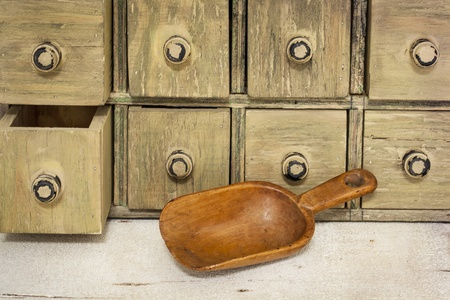 empty rustic wooden scoop with a primitive apothecary drawing cabinet in a background Stock Photo - 20440012