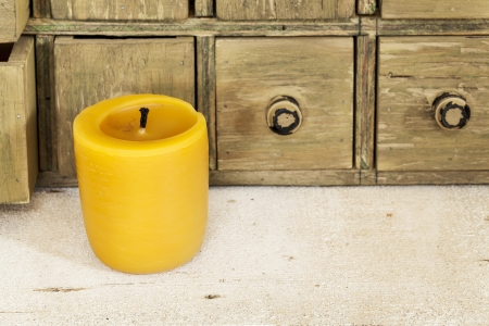 bee wax candle in retro setting with a primitive apothecary drawer cabinet Stock Photo - 20471537