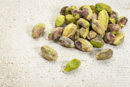 a pile of raw pistachio nuts on a rough white painted barn wood background Stock Photo - 20471533