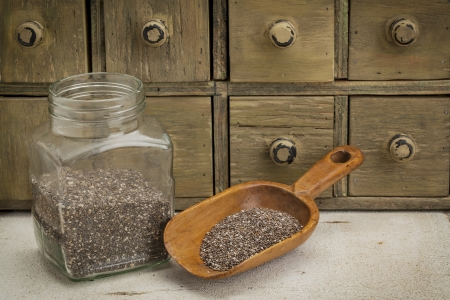 jar and scoop of chia seeds with a primitive apothecary drawer cabinet Stock Photo