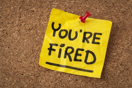 you are fired note - handwriting on orange sticky note Stock Photo