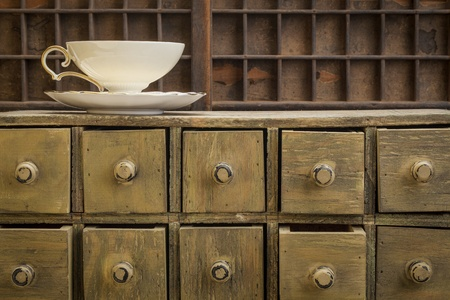 classic tea cup on top of rustic apothecary drawer cabinet Stock Photo - 20590324