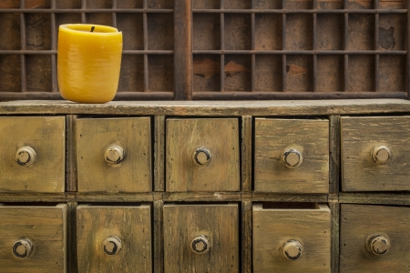 bee wax candle in retro setting with a primitive apothecary drawer cabinet Stock Photo - 20590332