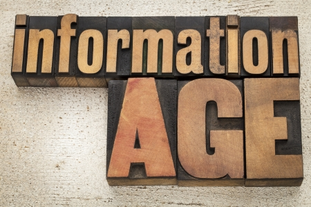 information age  in vintage letterpress wood type on a grunge painted barn wood background Stock Photo - 20590331