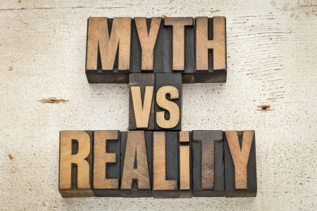 myth versus reality - concept  in vintage letterpress wood type on a grunge painted barn wood background Stock Photo - 20590326