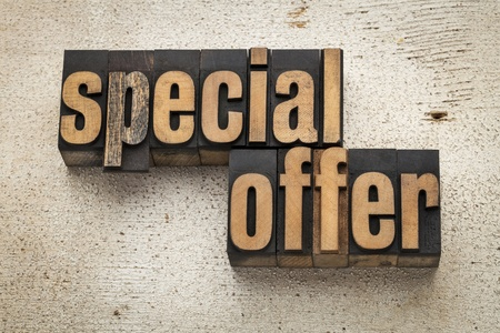 special offer sign in vintage letterpress wood type on a grunge painted barn wood background Stock Photo - 20590328