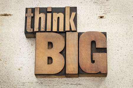 think big - motivation concept in vintage letterpress wood type on a grunge painted barn wood background Stock Photo - 20590327