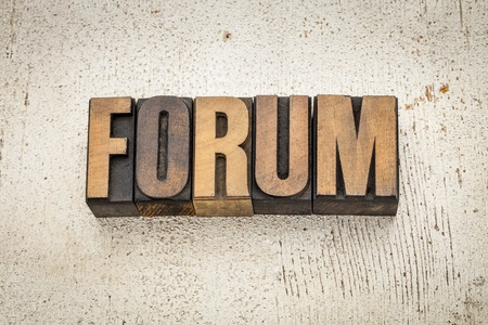 forum word in vintage letterpress wood type on a grunge painted barn wood background Stock Photo - 20832279