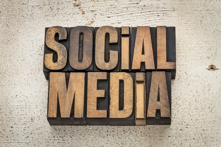 social media phrase in vintage letterpress wood type on a grunge painted barn wood background Stock Photo - 20832287