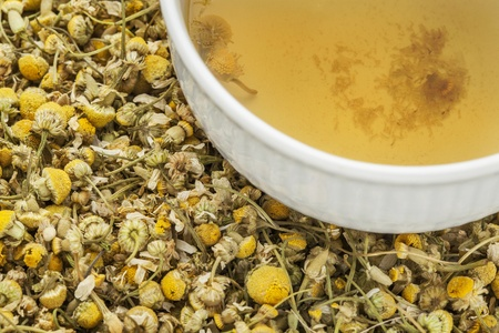 a cup of chamomile herbal tea with background of dry flowers photo