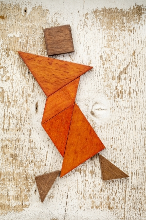 abstract figure of a female dancer built from seven tangram wooden pieces, a traditional Chinese puzzle game; rough white painted barn wood background photo