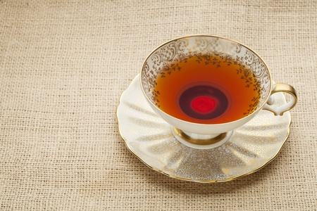afternoon tea - antique cup of black tea on canvas  (burlap)background Stock Photo - 20832333