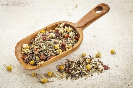 organic herbal tea (chamomile, peppermint,,orange peel, rose hips, hibiscus) - rustic wooden scoop and a pile on rough white painted barn wood Stock Photo - 20832341