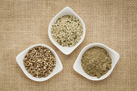 shelled: hemp products: seeds, hearts (shelled seeds) and protein powder in small ceramic bowls on burlap canvas